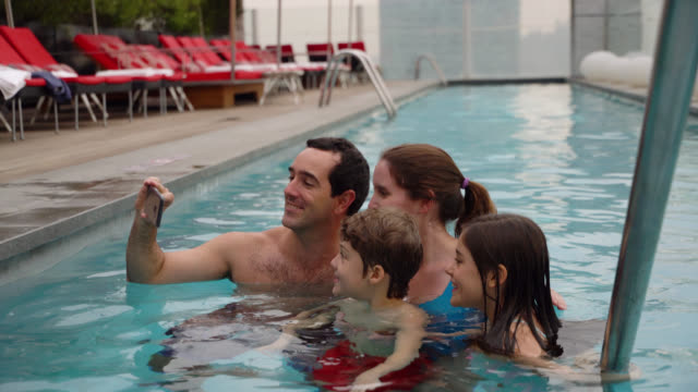 happy family enjoying a day at the pool taking a selfie with smartphone - tourist resort stock videos & royalty-free footage