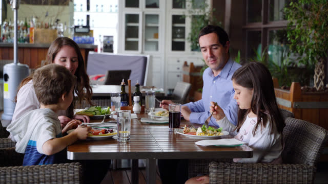happy family enjoying a delicious breakfast at the hotel restaurant talking and smiling - lunch stock videos & royalty-free footage