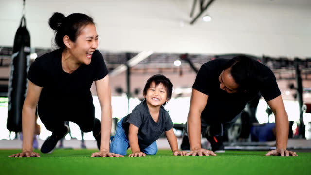 slo mo - happy family enjoying doing push ups in gym - asian stock videos & royalty-free footage
