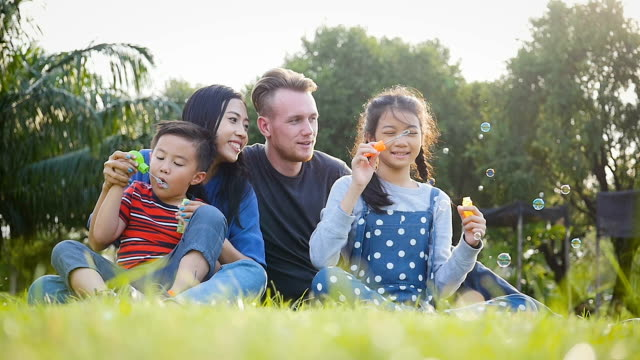 happy family enjoying playing with soap bubbles in autumn park - young family stock videos & royalty-free footage