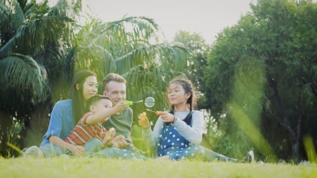 vidéos et rushes de héhé, profiter de jouer avec des bulles de savon dans le parc de plein air - jeune famille