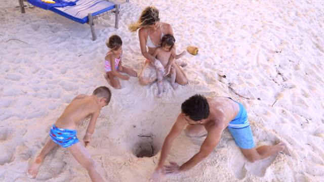 vídeos de stock, filmes e b-roll de família feliz curtindo enquanto brincava na areia durante o dia de verão na praia. - buraco