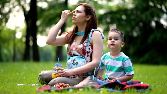Happy Family Expecting Newborn Tasting Fresh Strawberries On Picnic Day