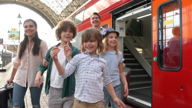 happy family getting down from train ready to do some tourism - conductor stock videos & royalty-free footage