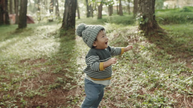 男の子の赤ちゃんに良い時間を過ごして幸せな家族 - 帽子点の映像素材/bロール