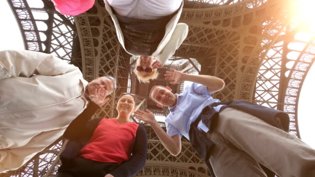 Happy family having fun and sending greetings under the Eiffel Tower in Paris in slow motion in 4k