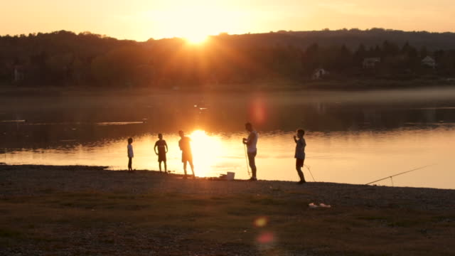 happy family having fun on vacation near lake during beautiful sunset - fishing stock videos & royalty-free footage