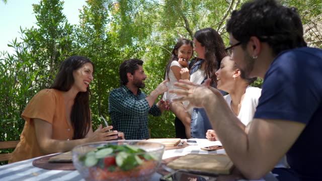 vídeos de stock, filmes e b-roll de família feliz que tem o bom tempo no almoço ao ar livre - almoço