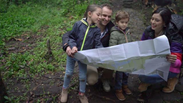 vidéos et rushes de heureuse famille randonnée dans la forêt et en regardant une carte - être perdu