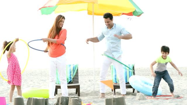 vidéos et rushes de ms happy family hula hooping on beach / india - hommes d'âge moyen