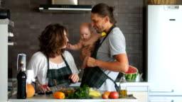 Happy family in their kitchen. A young mother prepares a salad and dad carries the baby in her arms. Mom kisses a child, dad kisses mom. Family idyll