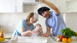 Happy Family is Cooking in The Kitchen. Dad Sifts Flour Slow motion
