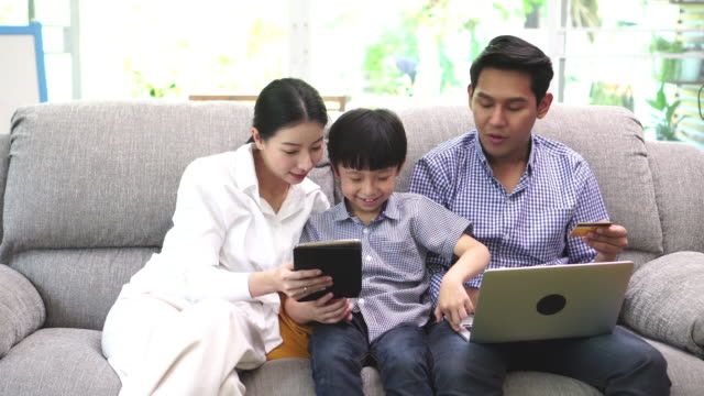 happy family is shopping online on laptop and tablet - adult imitation stock videos and b-roll footage