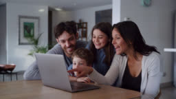 Happy family looking at videos on laptop while kids point at screen and talk smiling