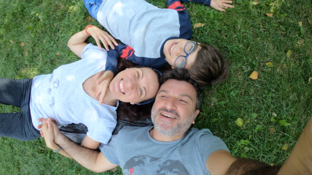 happy family lying on grass - sdraiato video stock e b–roll