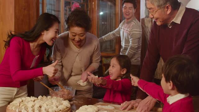 happy family making dumplings at home,4k - ダンプリング点の映像素材/bロール
