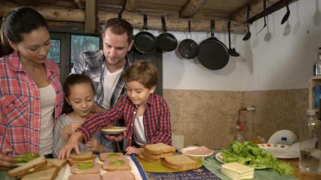 vídeos de stock, filmes e b-roll de família feliz fazendo sanduíches para o jantar - sanduíche