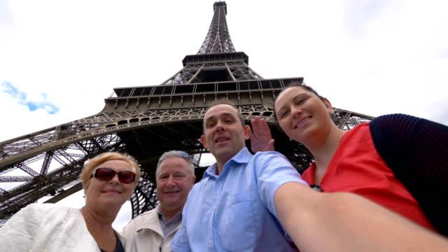 Happy family making selfie under the Eiffel Tower in Paris in slow motion in 4k