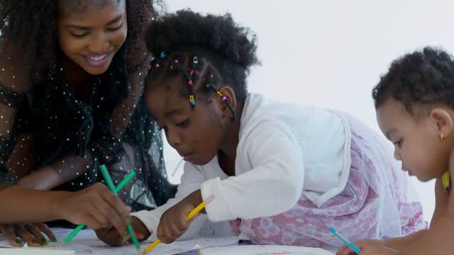 vidéos et rushes de famille heureuse de mère africaine avec le petit âge de deux bébés 1,2 ans suçant le bonbon doux mignon tout en homeschooling restent à la maison. la jeune mère de parent enseignant l'enfant d'école aide à étudier à la maison. homeschooling  - new age concept