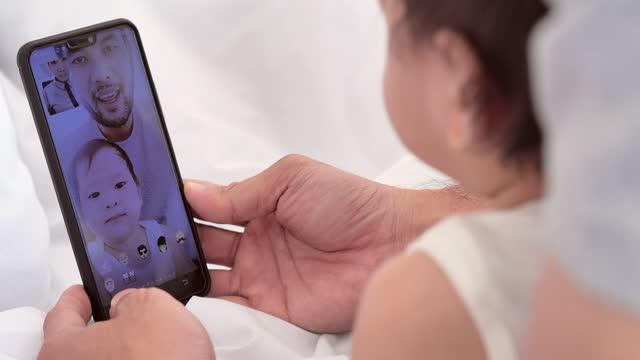 vidéos et rushes de famille heureuse de père asiatique et le nouveau-né 10 mois sur la vidéoconférence pour appel à la mère ou des parents pendant la distanciation sociale ensemble rester à la maison pour prévenir les épidémies de coronavirus ou covide-19.people sur - new age concept