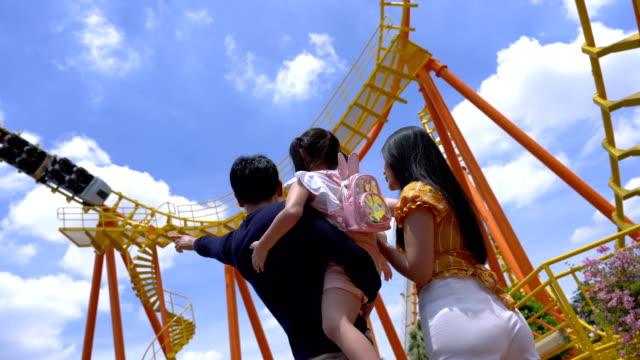 vidéos et rushes de une famille heureuse de mère, de père et d'enfants, de fille, s'amusant en vacances dans un parc d'attractions - parc d'attractions