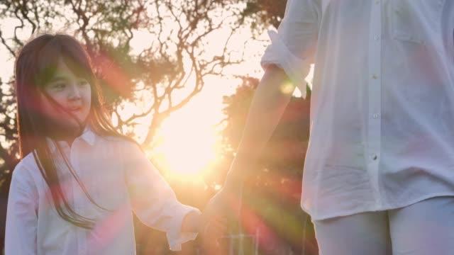 夏の自然散策には幸せな家族がいます。女性は日没の間に屋外で彼女の小さな魅力的な娘と時間を過ごしています。リラックスした子育て - 手をつなぐ点の映像素材/bロール