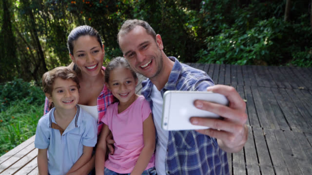 happy family outdoors sitting on a deck taking a selfie smiling - photographing stock videos and b-roll footage