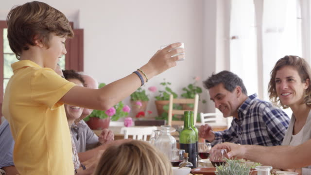 happy family raising toast at dining table - multi generation family stock videos & royalty-free footage