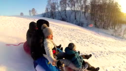 happy family rides and smiling snowtube on snowy roads.slow motion. snow winter landscape. outdoors sports