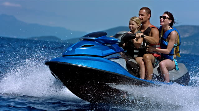slo mo happy family riding a jet boat - jet ski stock videos & royalty-free footage