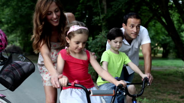 happy family riding bicycles in a park. - help single word stock videos and b-roll footage