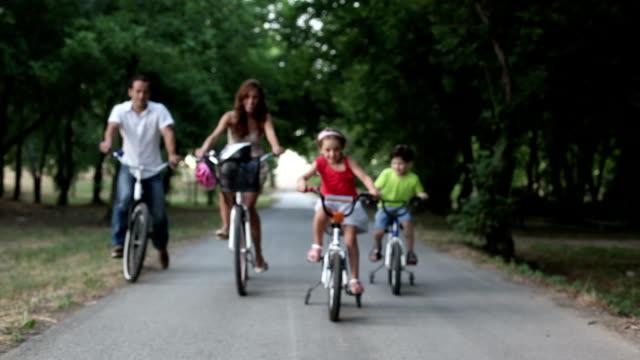 Glückliche Familie Reiten Fahrräder in einem park.