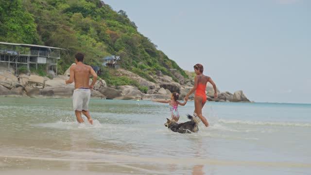glückliche familie läuft am strand - tropical climate stock-videos und b-roll-filmmaterial