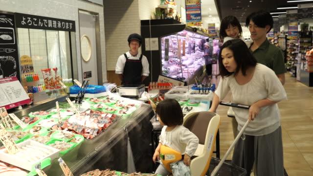 幸せな家族のショッピングのスーパーマーケット