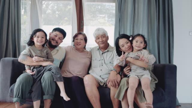 自宅でソファに座って幸せな家族 - 民族点の映像素材/bロール