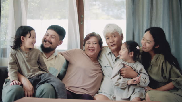 happy family sitting on sofa at home - life events stock videos & royalty-free footage