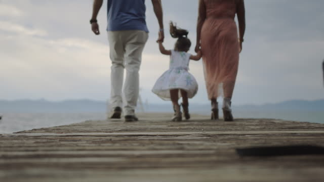 vídeos de stock, filmes e b-roll de happy family skipping on a dock slow motion - dois genitores