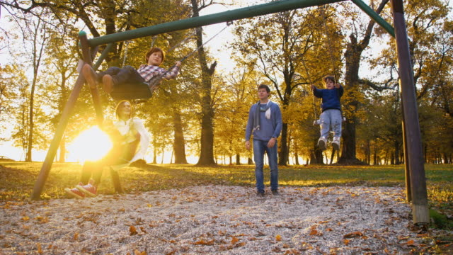slo mo happy family swinging in the park - swing play equipment stock videos and b-roll footage