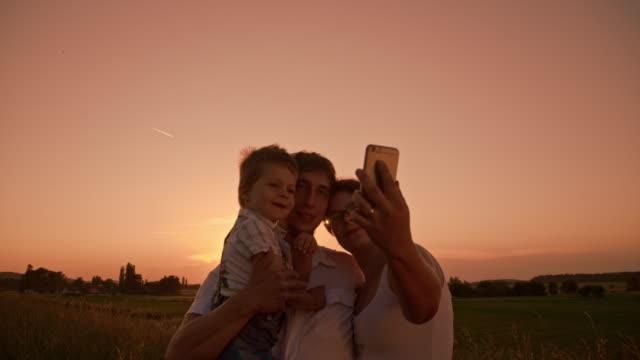 幸せな家族の中で自分撮りに沈む夕日 - 幼児点の映像素材/bロール