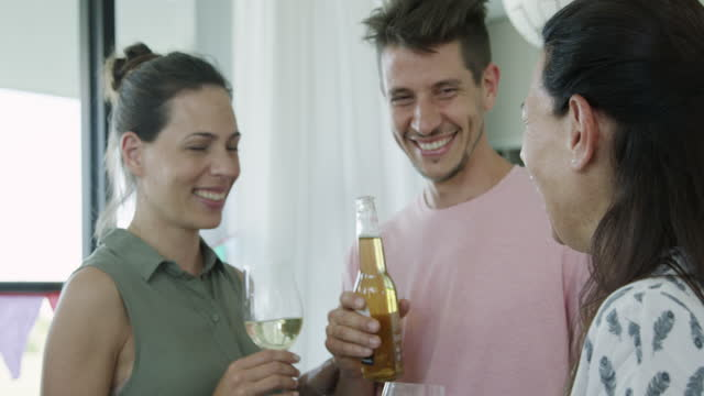 happy family toasting wine glasses and beer bottles while standing in living room - fade in video transition stock videos & royalty-free footage