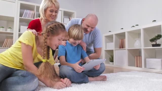 hd dolly: happy family using tablet - bonding stock videos & royalty-free footage