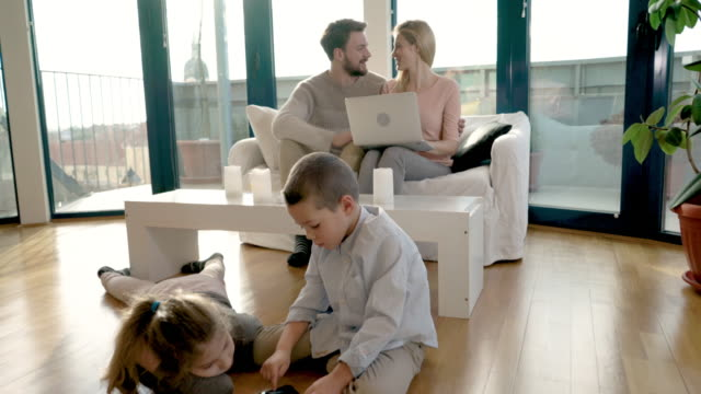 Happy family using wireless technology while relaxing at their apartment.