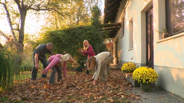 vídeos de stock e filmes b-roll de carrinho de hd: família feliz - ancinho equipamento de jardinagem