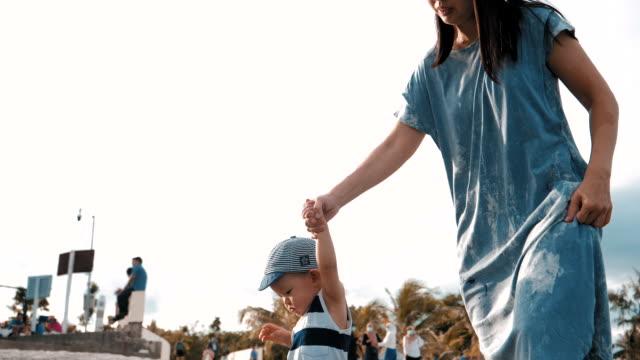 glückliche familie zu fuß am strand - 6 11 months stock-videos und b-roll-filmmaterial