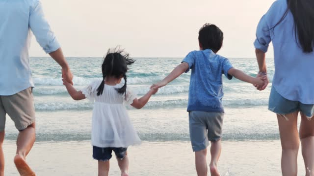 happy family walking together on the beach.happy family enjoy summer vacation on the beach.vacations - istock - moving image video stock e b–roll