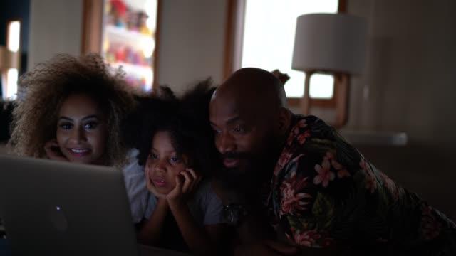 vídeos de stock, filmes e b-roll de filme de observação da família feliz em um portátil - aconchegante
