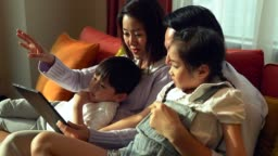 Happy family watching tablet in the living room.