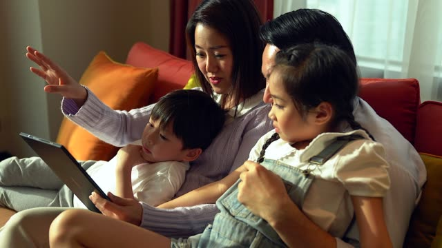 happy family watching tablet in the living room. - family stock videos & royalty-free footage