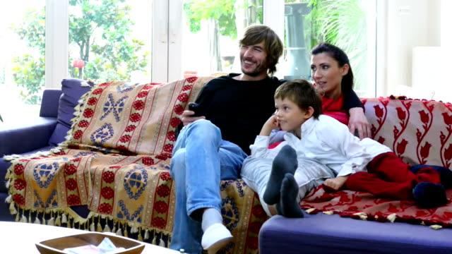 türkische familie sitzen auf der couch vor dem fernseher - real wife sharing stock-videos und b-roll-filmmaterial