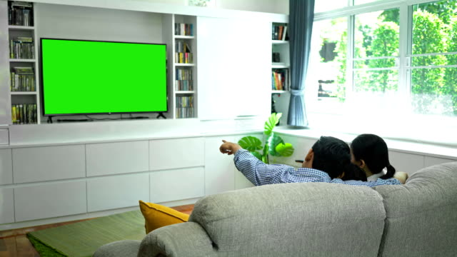 4k happy family watching tv with green screen monitor in living room - guardare la tv video stock e b–roll